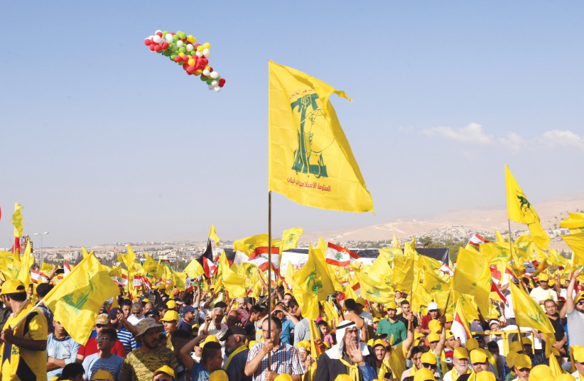 SUPPORTERS OF Hezbollah leader Sayyed Hassan Nasrallah display Hezbollah and Lebanese flags in Baalbek, Bekaa valley in eastern Lebanon in August last year. (Hassan Abdallah/Reuters) (photo credit: HASSAN ABDALLAH / REUTERS)