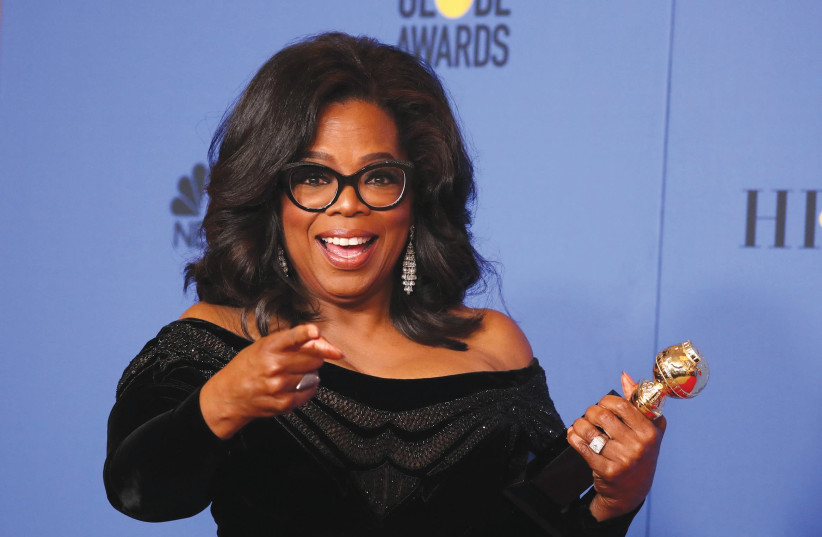 Oprah Winfrey poses backstage with her Cecil B. DeMille Award at the 75th Golden Globe Awards in Beverly Hills, California, last week (photo credit: REUTERS/LUCY NICHOLSON)