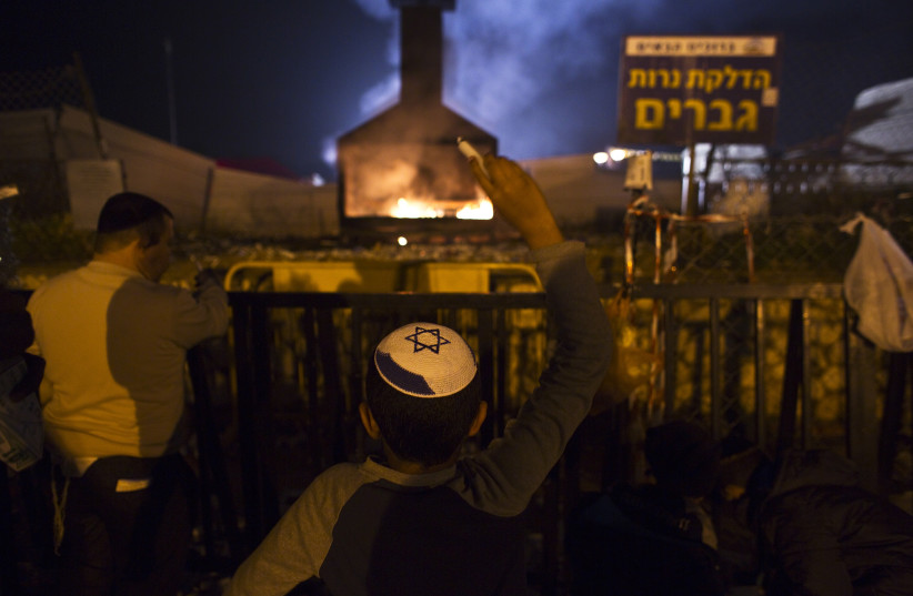 A Jewish worshipper throws candles into a fire during an annual pilgrimage to the gravesite of Rabbi Yisrael Abuhatzeira, a Moroccan-born sage and kabbalist also known as the Baba Sali. (photo credit: REUTERS)