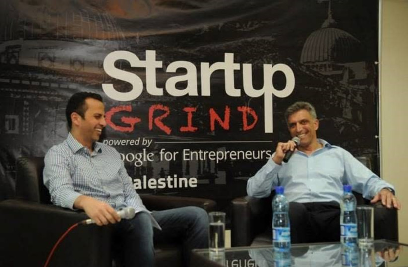Israeli venture capitalist Yadin Kaufmann, a major investor in Palestinian startups, sits down with Palestinian entrepreneur Peter Abualzolof at a conference in Ramallah in 2014.  (photo credit: Courtesy)
