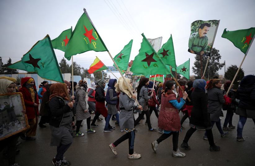 People hold flags of Women's Protection Unit (YPJ) as they walk during a protest against Turkish attacks on Afrin, in Hasaka, Syria, January 18, 2018. (photo credit: RODI SAID / REUTERS)