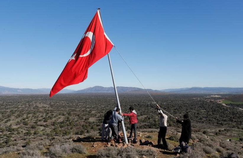 Villagers fix a broken flagpole in Sugedigi village on the Turkish-Syrian border in Hatay province, Turkey January 20, 2018 (photo credit: REUTERS/OSMAN ORSAL)