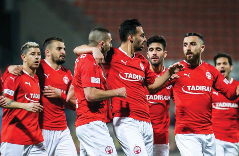 Hapoel Beersheba players celebrate after Ben Sahar (third from left) netted the winner in a 1-0 victory at Hapoel Acre. (photo credit: MAOR ELKASLASI)
