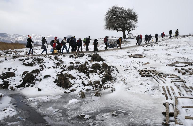 Migrants cross a snowy field, January 2016 (photo credit: MARKO DJURICA / REUTERS)