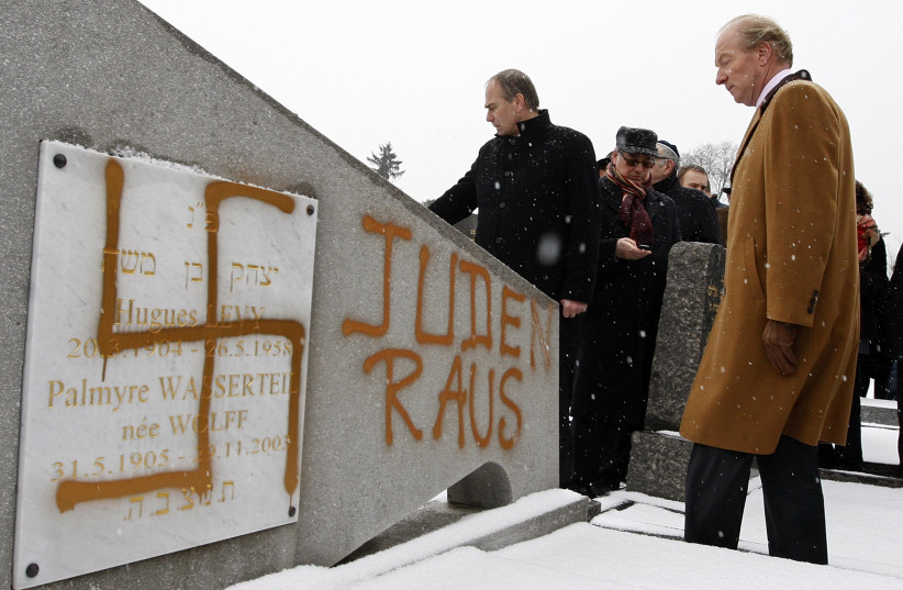 """France's Interior Minister Brice Hortefeux walks next to a tombstone desecrated by vandals with a Nazi swastika and the Slogan """"Jews Out"""", in the Jewish Cemetery of Cronenbourg near Strasbourg (photo credit: VINCENT KESSLER/ REUTERS)"""