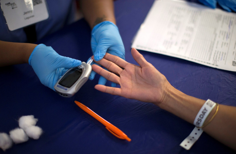 A person receives a test for diabetes during Care Harbor LA free medical clinic in Los Angeles, California September 11, 2014.  (photo credit: MARIO ANZUONI/REUTERS)