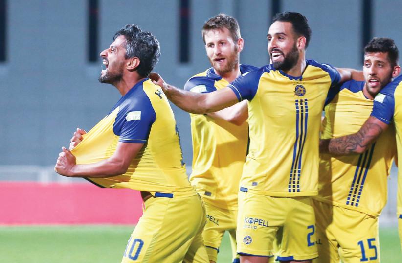 Maccabi Tel Aviv striker Barak Itzhaki (left) celebrates with teammates after scoring his team's second goal in last night's 3-1 win over Hapoel Ashkelon. (photo credit: DANNY MARON)