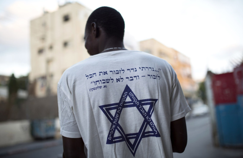 "An African refugee in south Tel Aviv wears a T-shirt with a Hebrew phrase referring to the Holocaust: ""I promise to remember... and never forget!"" (photo credit: REUTERS)"