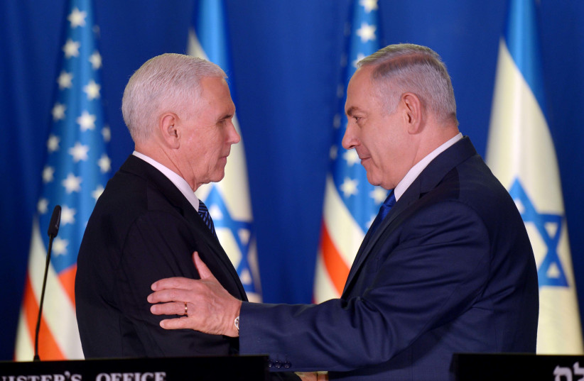Prime Minister Benjamin Netanyahu and United States Vice President Mike Pence embrace during joint speeches on January 22, 2018. (photo credit: AVI OHAYON - GPO)