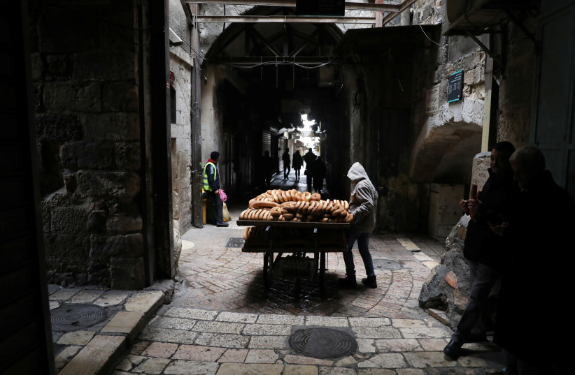 A man sells bread in the nearly-empty Muslim quarter of Jerusalem's Old City during the Palestinian's general strike against US VP Pence's visit, January 2018 (photo credit: AMMAR AWAD/REUTERS)