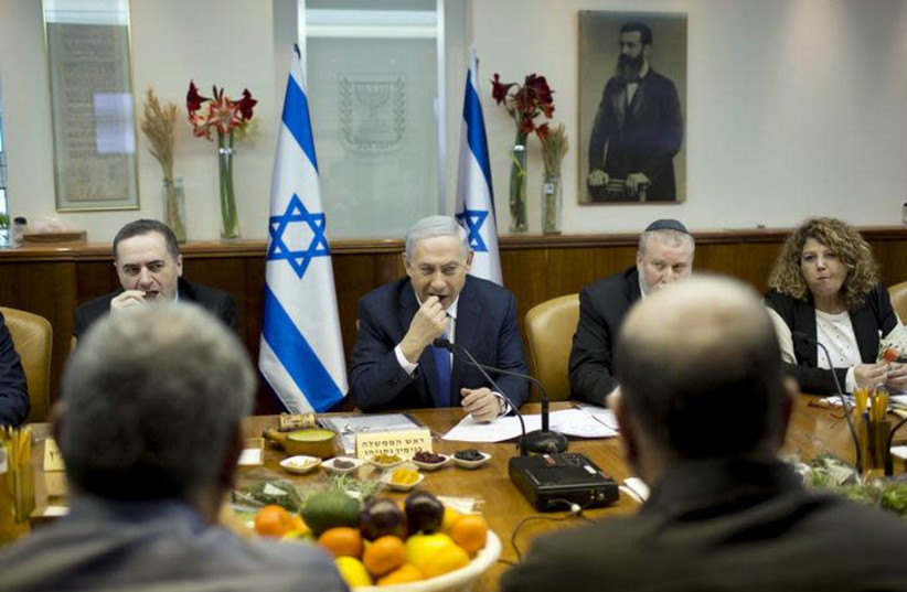 sraeli Prime Minister Benjamin Netanyahu (C) eats fruits and nuts as he marks Tu Bishvat, the Jewish Arbor Day, during the weekly cabinet meeting at his office in Jerusalem January 24, 2016. (photo credit: ABIR SULTAN / REUTERS)