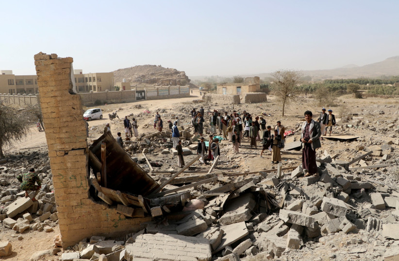 People gather at the site of an air strike that destroyed a house on the outskirts of the northwestern city of Saada, Yemen January 22, 2018. (photo credit: NAIF RAHMA / REUTERS)
