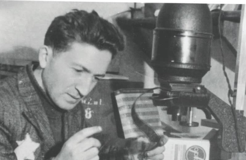 MENDEL GROSSMAN works in his photography lab in the Lodz Ghetto. Many of Grossman's photos depict the suffering in the ghetto and were found after the war, outliving their creator.  (Yad Vashem Photo Archives) (photo credit: COURTESY: YAD VASHEM PHOTO ARCHIVE)
