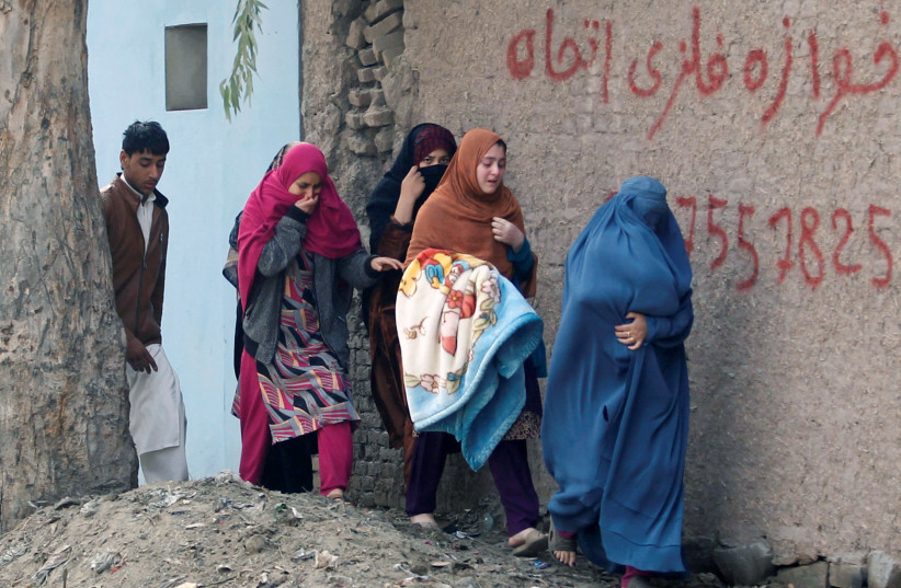 Afghan women leave the site of a blast and gun fire in Jalalabad. (photo credit: REUTERS/PARWIZ)