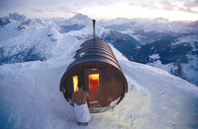 A MAN enters a sauna on the peak of Mount Lagazuoi in Cortina D'Ampezzo, Italy (photo credit: STEFANO RELLANDINI/REUTERS)
