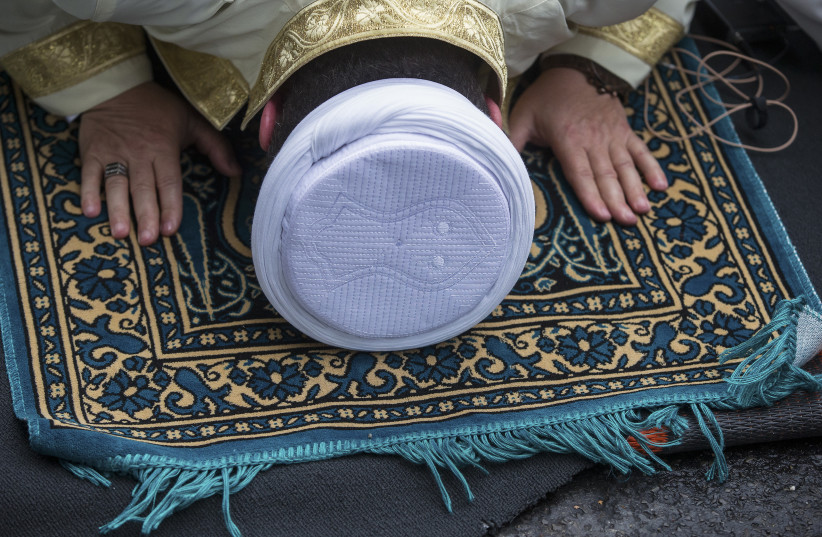 An Imam performs Friday prayers on Skalitzer Strasse (street) in Berlin September 19, 2014. (photo credit: REUTERS)