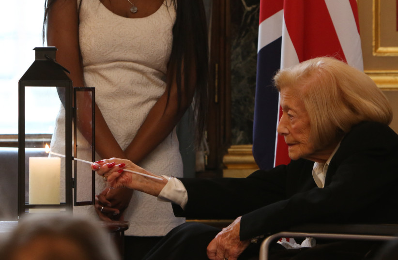 Holocaust survivor Gena Turgel MBE lights a candle at the British Foreign & Commonwealth Office's Holocaust Memorial Day event, 23 January 2018. (photo credit: FOREIGN & COMMONWEALTH OFFICE)