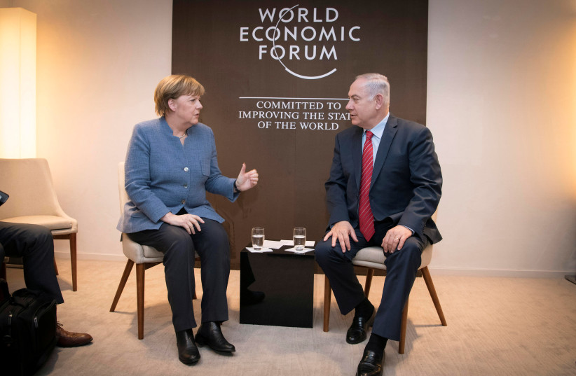 German Chancellor Angela Merkel meets Israeli Prime Minister Benjamin Netanyahu during the World Economic Forum (WEF) annual meeting in Davos, Switzerland January 24, 2018. (photo credit: BUNDESREGIERUNG/GUIDO BERGMANN/HANDOUT VIA REUTER)