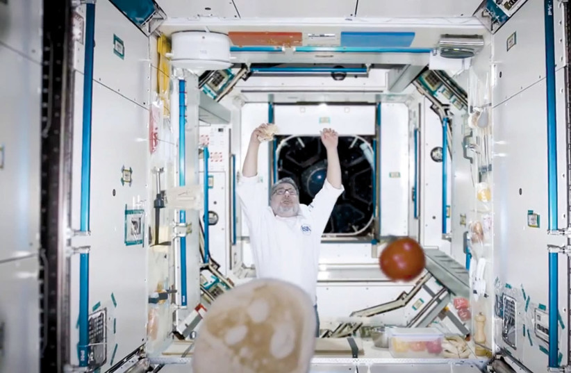 CHEF HAIM COHEN tries to make a falafel in a reenactment of space for the Science and Technology Ministry's Space Week activities, which are launched on January 28, 2018.. (photo credit: screenshot)