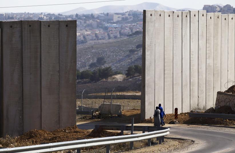 Palestinians walk near an opening in Israel's barrier in the east Jerusalem neighborhood of A-tur January 3, 2014. (photo credit: RONEN ZVULUN / REUTERS)