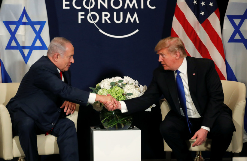 US President Donald Trump shakes hands with Israeli Prime Minister Benjamin Netanyahu during the World Economic Forum meeting in Davos, Switzerland (photo credit: CARLOS BARRIA / REUTERS)