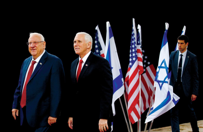US VICE President Mike Pence walks alongside President Reuven Rivlin during a formal reception ceremony at Beit Hanassi on Tuesday. (Ronen Zvulun/Reuters). (photo credit: RONEN ZVULUN/REUTERS)
