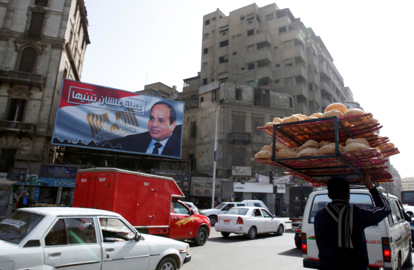 """A busy street near a poster of Egypt's President Abdel Fattah al-Sisi from the campaign titled """"Alashan Tabneeha"""" (So You Can Build It), for the upcoming presidential election in Cairo, Egypt, January 22, 2018. (photo credit: REUTERS)"""