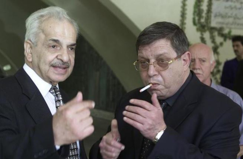 Ghassan al-Shakaa (R) member of the Palestinian Liberation Organisation (PLO) talks to Mahmoud al-Khalidi, then Palestinian ambassador to Syria on September 25, 2001. (REUTERS / Khaled al-Hariri) (photo credit: REUTERS/KHALED AL-HARIRI)