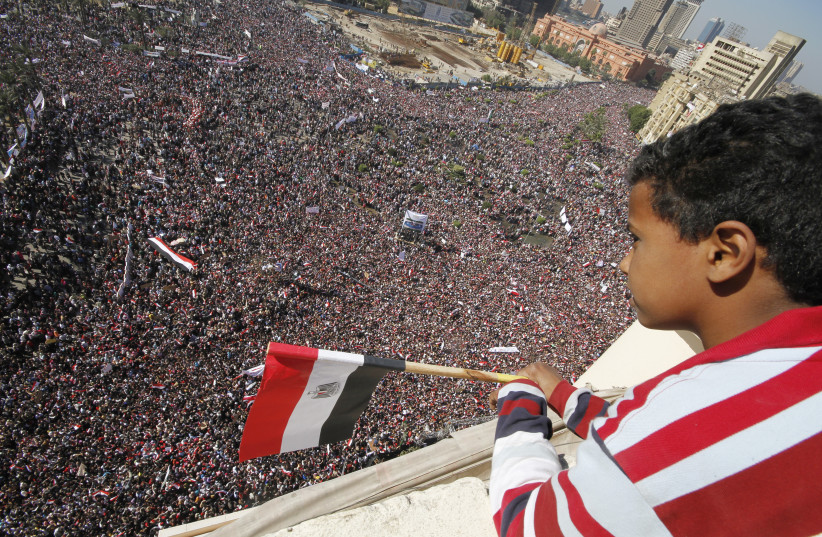 A boy watches as pro-democracy supporters gather in Tahrir Square in Cairo February 18, 2011. (photo credit: REUTERS)
