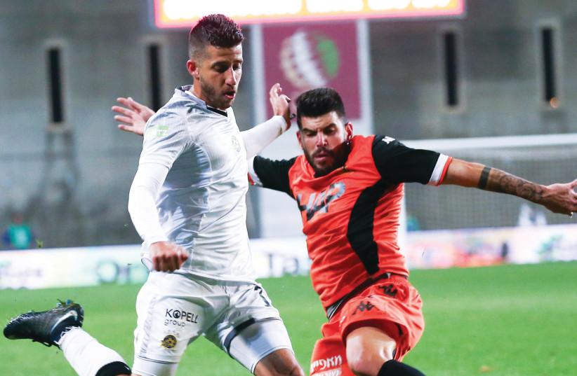 Maccabi Tel Aviv midfielder Dor Micha (left) is tackled by Bnei Yehuda's Ben Turgeman (right) during last night's 0-0 draw in Petah Tikva. (photo credit: DANNY MARON)