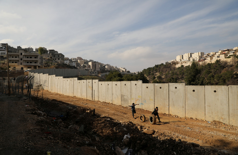 Children roll tires as they run along the Israeli security barrier wall in the east Jerusalem refugee camp of Shuafat on January 3, 2018.  (photo credit: AMMAR AWAD / REUTERS)