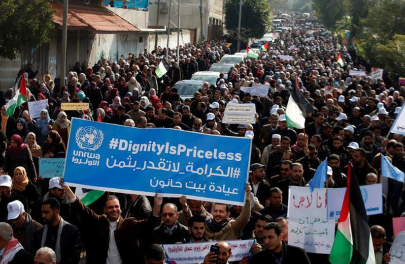 Palestinian employee of United Nations Relief and Works Agency (UNRWA) hold a sign during a protest against a US decision to cut aid, in Gaza City January 29, 2018. (REUTERS/Mohammed Salem) (photo credit: REUTERS/MOHAMMED SALEM)