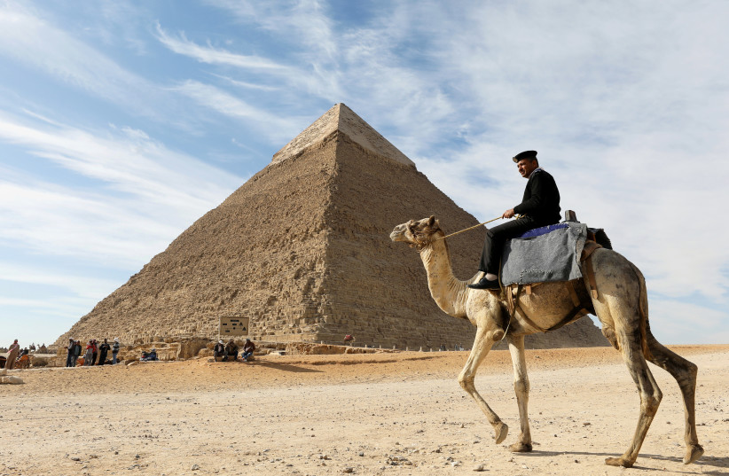 A police officer patrols the Giza Pyramids on his camel on the outskirts of Cairo, Egypt December (photo credit: MOHAMED ABD EL GHANY/REUTERS)
