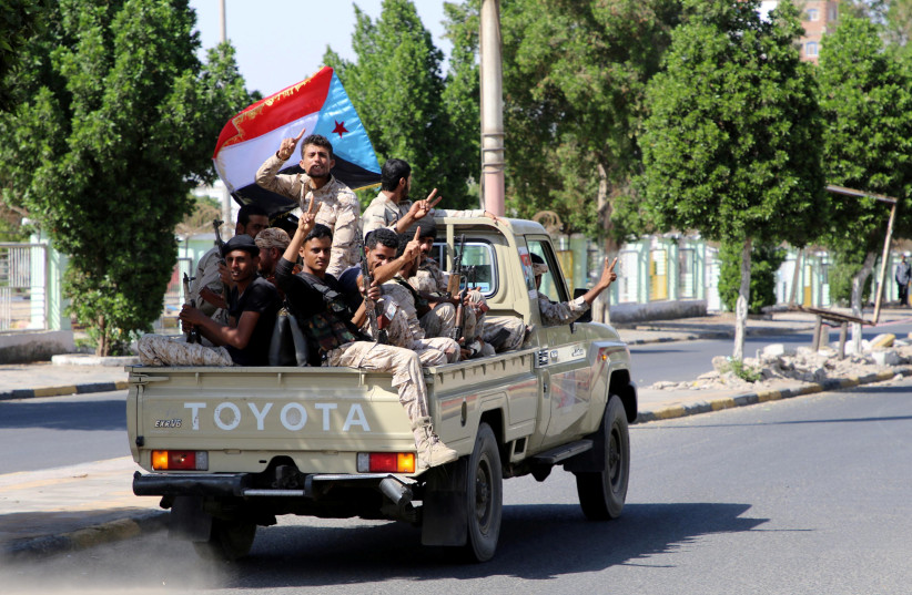 Southern Yemeni separatist fighters flash the V sign as they ride on the back of a truck in Aden, Yemen (photo credit: FAWAZ SALMAN/REUTERS)
