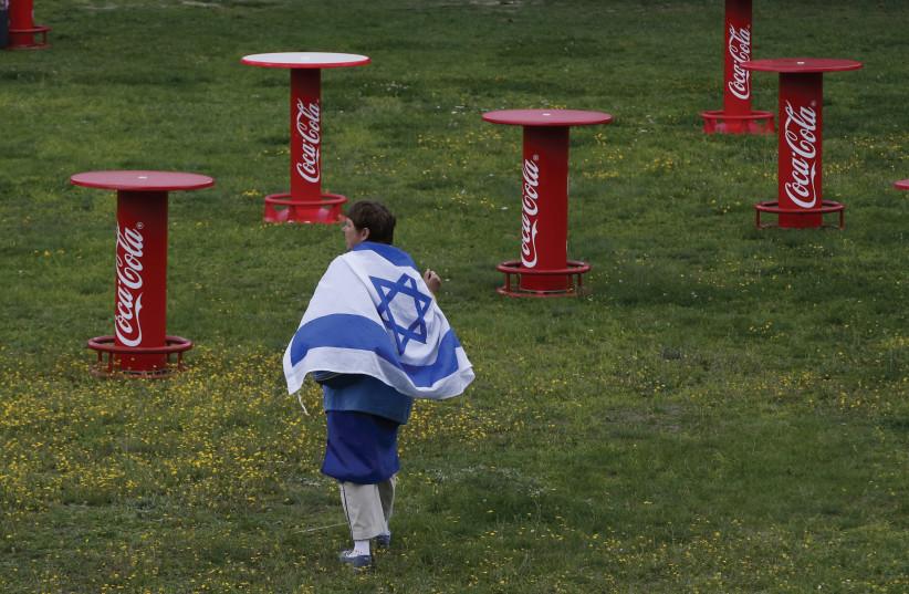 Man walks with Israeli flag in Berlin  (photo credit: REUTERS)