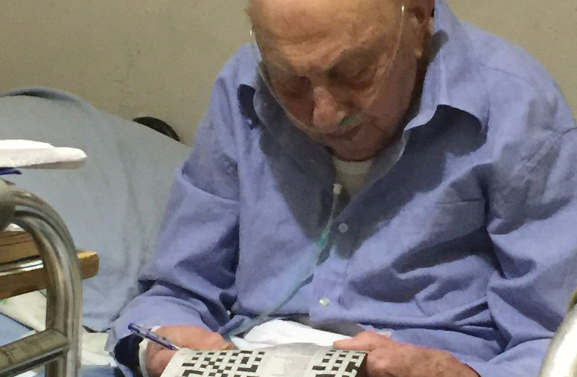 Herb Selig solves 'The Jerusalem Post' crossword puzzle earlier this month (photo credit: Courtesy)