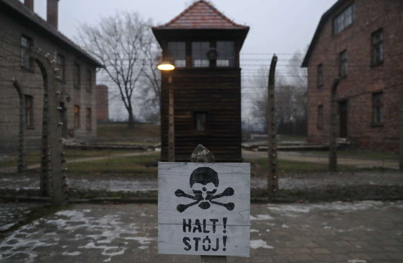 "A sign reading ""Stop"" in German and Polish is placed outside the gates to Auschwitz to mark the anniversary of its liberation, January 2018 (photo credit: KACPER PEMPEL/REUTERS)"
