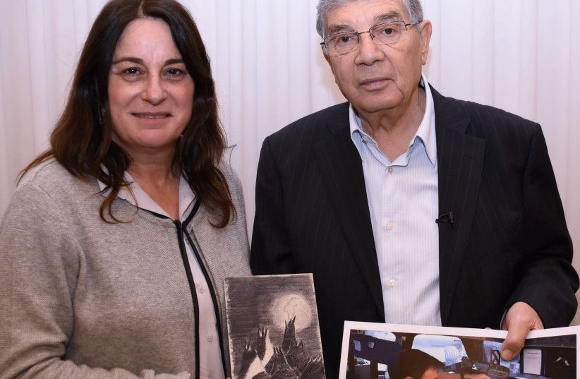 """Rona Ramon holding a picture of Ilan Ramon with a copy of the """"Moon Landscape"""" before his mission to space in 2003; also in the picture NASA Astronaut Tom Marsburn and his wife Ann, who are attending the Israel Space Week events. (photo credit: DANIEL BABCZYK/YAD VASHEM)"""