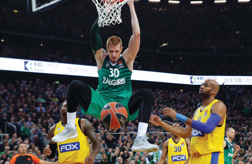 Maccabi Tel Aviv center Alex Tyus (right) looks on helplessly as Zalgiris Kaunas big man Aaron White (center) dunks for two of his eight points during a 99-84 defeat in Lithuania. (photo credit: UDI ZITIAT)