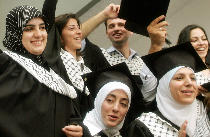 Palestinian students celebrate following a graduation ceremony at Al-Najah University in the West Bank city of Nablus. (photo credit: ABED OMAR QUSINI/REUTERS)