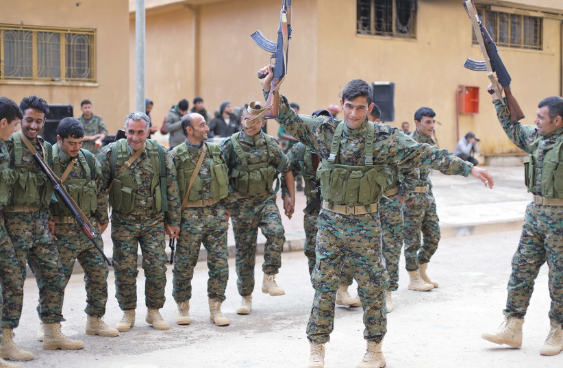 FIGHTERS FROM a new internal security force under the command of the Syrian Democratic Forces dance during a graduation ceremony last month in Hasaka, in northeastern Syria (photo credit: REUTERS/RODI SAID)