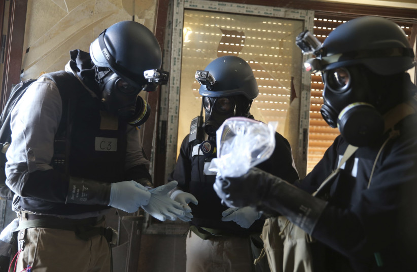 UN chemical weapons experts inspect alleged chemical samples from an attack in Syria, 2013 (photo credit: STRINGER/ REUTERS)