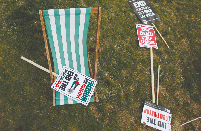 ANTI-ISRAEL SIGNS sit on a field after an anti-Israel rally in London (photo credit: REUTERS)