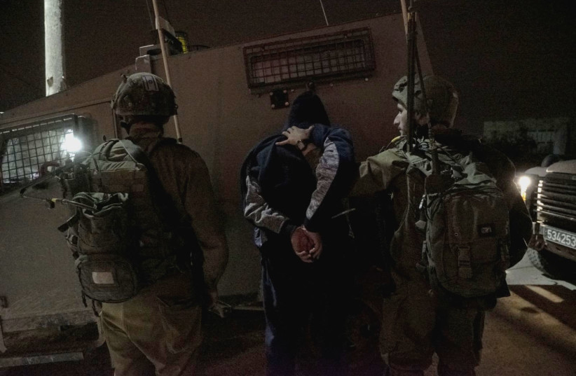 Israeli forces arrest a man in the West Bank village of Al-Yamun during a raid (photo credit: IDF SPOKESPERSON'S UNIT)