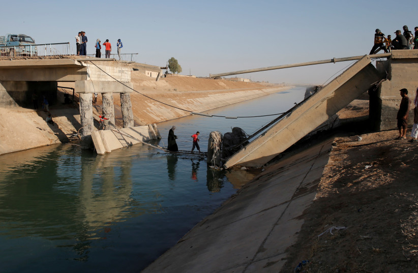 People cross a makeshift ladder in a village near Raqqa after a bridge was destroyed in fighting between the US-led coalition and Islamic State, in Raqqa, Syria, June 16, 2017 (photo credit: GORAN TOMASEVIC/REUTERS)