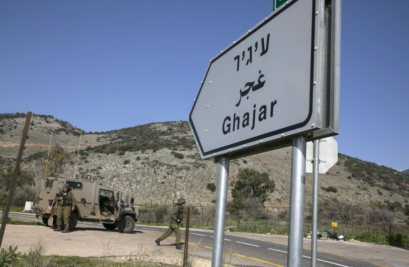 Israeli soldiers are seen next to a sign post pointing to the village of Ghajar near Israel's border with Lebanon (photo credit: BAZ RATNER/REUTERS)