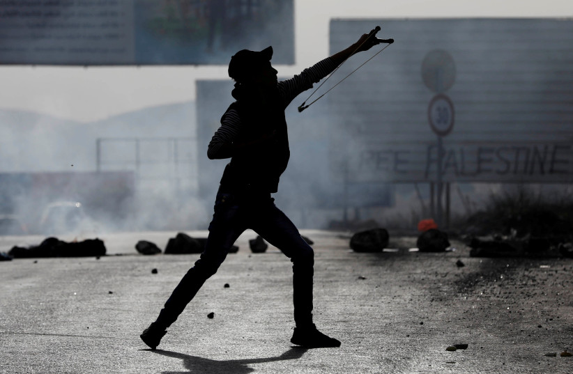 A masked Palestinian demonstrator uses a slingshot to hurl stones towards Israeli troops during clashes near the West Bank city of Nablus, December 29, 2017. (photo credit: REUTERS/MOHAMAD TOROKMAN)
