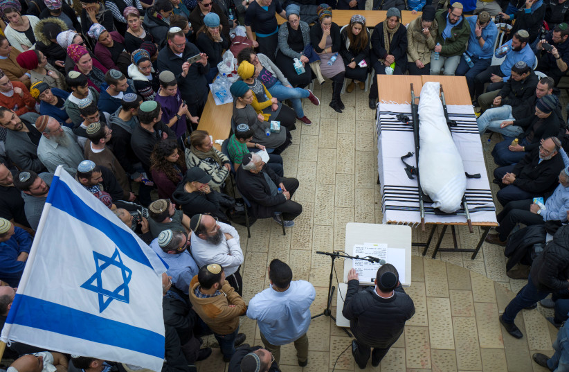 Relatives and friends mourn as they stand around the body of Itamar Ben Gal, an Israeli killed in a stabbing attack on February 5, during his funeral in the Jewish settlement of Har Bracha in the West Bank, February 6, 2018.  (photo credit: REUTERS/JIM HOLLANDER/POOL)