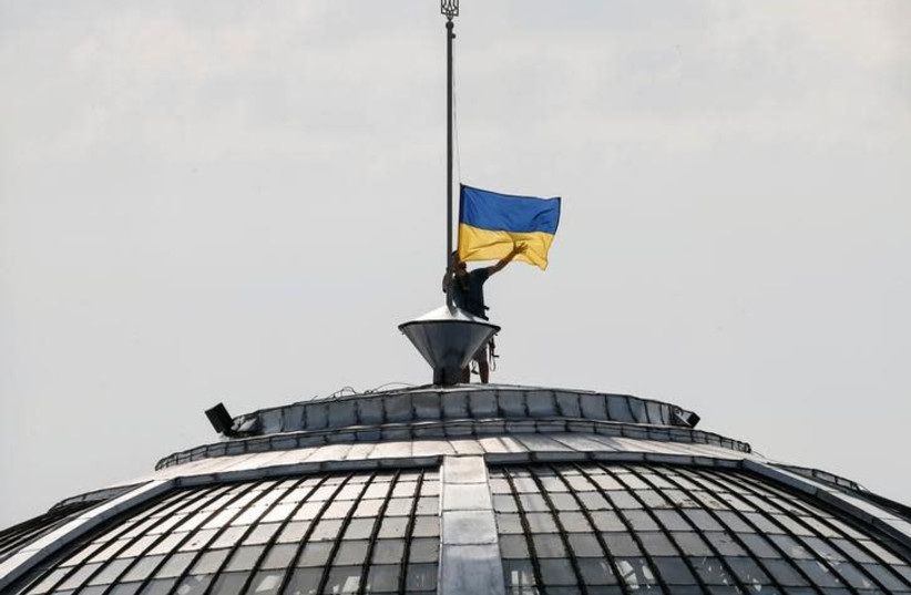 A climber installs the Ukrainian national flag on a roof, marking the Day of the State Flag, on the eve of the Independence Day, in Kiev, Ukraine, August 23, 2016 (photo credit: GLEB GARANICH/REUTERS)