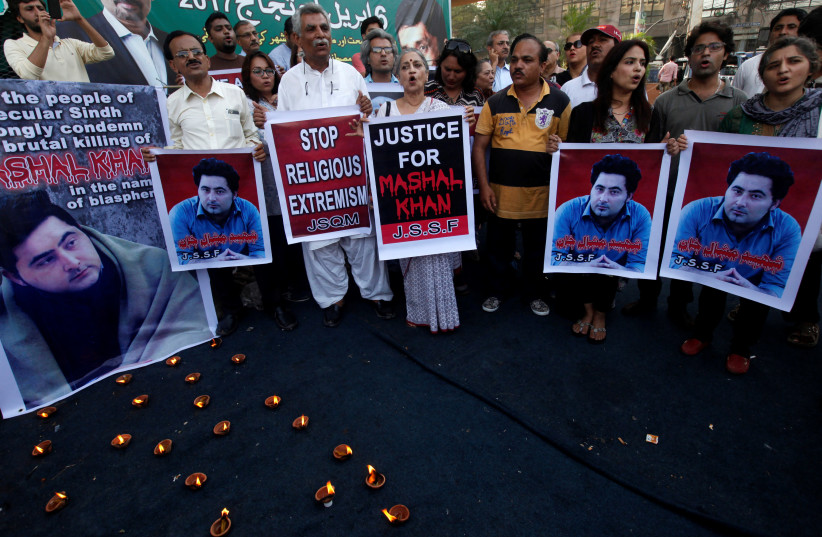 People hold signs as they chant slogans to condemn the killing of Mashal Khan, student of Abdul Wali Khan University after he was accused of blasphemy, during a protest in Karachi, Pakistan, April 22, 2017.  (photo credit: REUTERS/AKHTAR SOOMRO)
